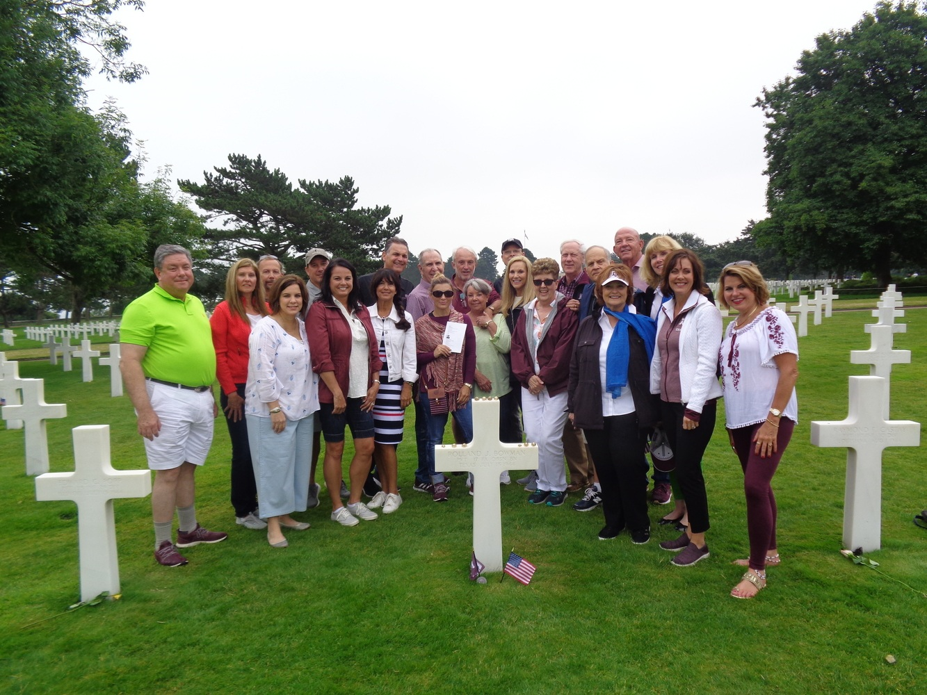 A group of people next to a grave in Normandy
